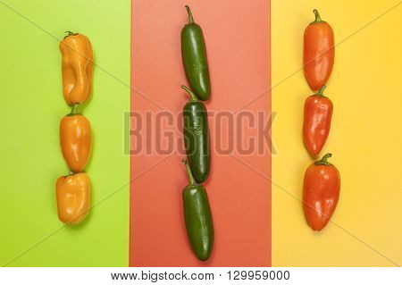 Various peppers on bright multi colored background.