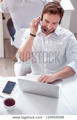Zealous worker. Positive handsome smiling man sitting at the table and working on the laptop in the office with his colleague while  using headset with micro