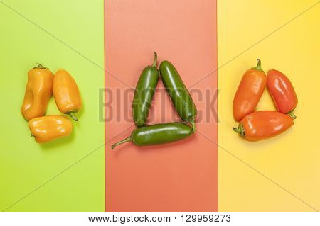 Groups of vivid color peppers on multicolor background.