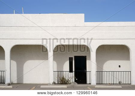 A modern side entrance with a porch of square pillars and beams in white paint.