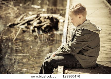 Single Boy In Jacket Sitting On Dock