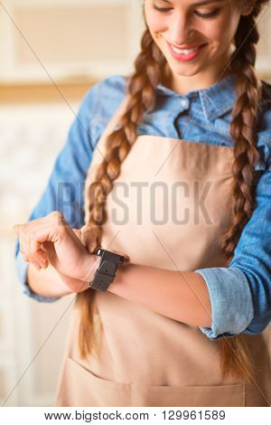 Stay in pace with time.  Pleasant cheerful beautiful smiling woman looking at her smart watch and expressing gladness, while standing in the kitchen