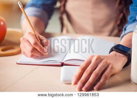 Put it down. Close up of pencil in hands of pleasant woman holding it and making notes while standing in the kitchen