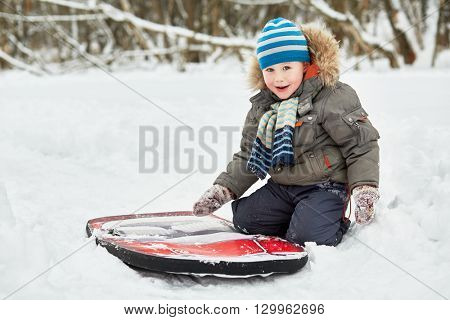 Little boy sits on snow near soft sledges in winter park.