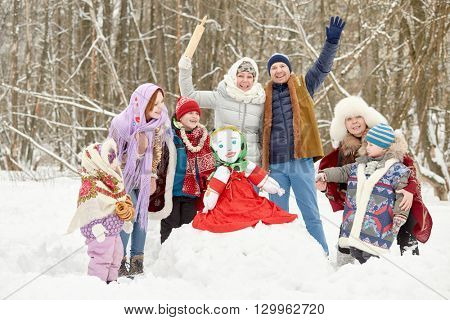 Three adults and four children around stuffed dummy Maslenitsa in winter park.