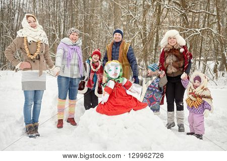 Three adults and four children stand holding hands around stuffed dummy Maslenitsa in winter park.