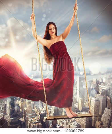 Girl on a swing above the city