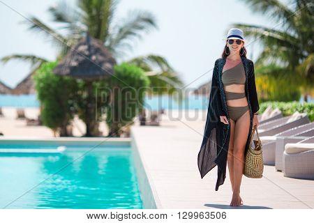 Young beautiful woman enjoying the luxurious quiet swimmingpool