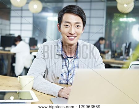 young asian businessman working in office using laptop computer.