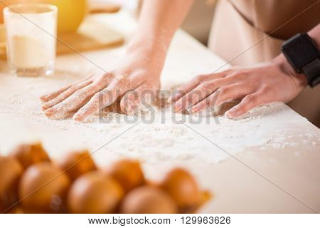 Make with love. Close up of hands of pleasant woman making dough and holding hands on the table while being involved in cooking