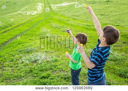 Two boys blowing up the soap bubbles on green lawn