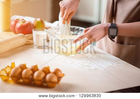 Mix it together. Close up of looped wire in hands of pleasant woman holding it and mixing ingredients while making bough