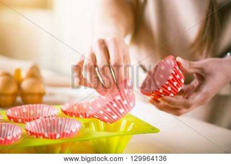 Nice  process.  Pleasant woman holding cake pans while baking in the kitchen