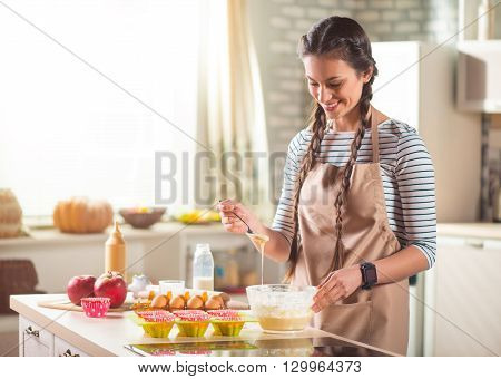 Best receipt. Pleasant delighted beautiful woman cooking dough and standing near table while going to bake cakes