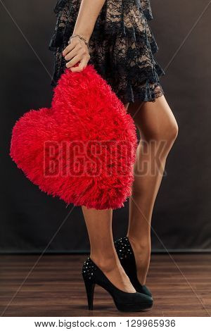Woman mid aged female wearing black evening dress holding big pillow in form of heart love symbol studio shot on black. Valentines day happiness concept