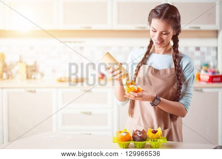 Charged with inspiration. Pleasant delighted smiling woman standing near table and decorating cakes while cooking in the kitchen