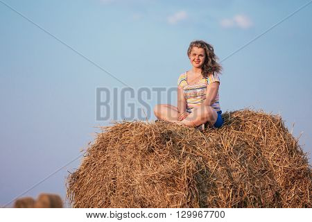 Beautiful Plus Size Young Woman In Shirt Sit On Hay Bales In Summer Field Meadow At Blue Sly Background