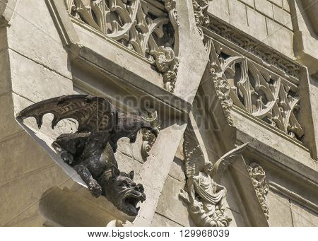Low angle shot of neo gothic style church details with grotesque dark figure as the main subject