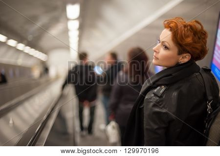Woman coming down to the metro station through the escalator tounel