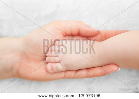 Newborn baby foot in mother's hand. Concept of child care, protection, parent love