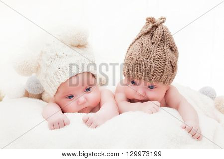 Twin sisters babies lying together wearing funny woolen bobble hats. White background