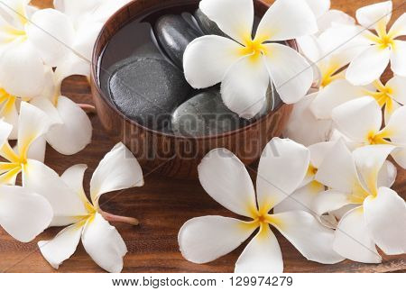 wooden bowl of stones with white frangipani on board