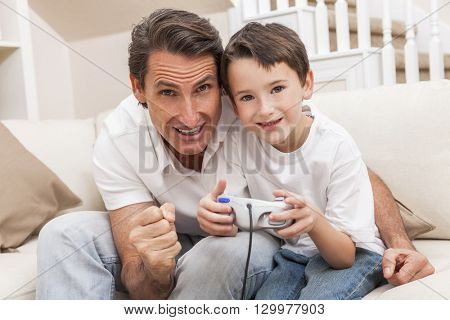 Man and male boy child, father and son having fun playing video computer console game together using handset controller on sofa at home