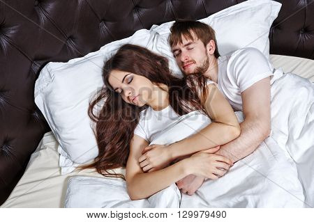 Married couple sleeping in bed. Sweet dreams. Marital bed.