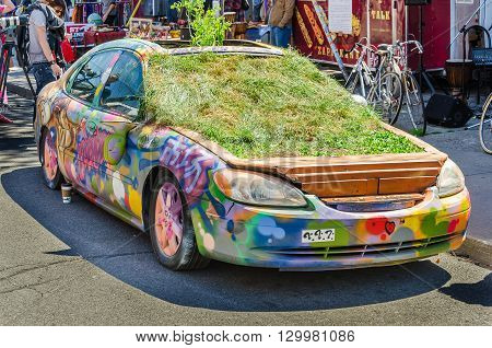 Car Down Kensington Market Covered In Grafitti And Plants