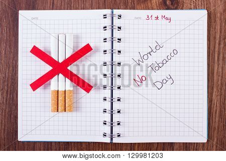 Cigarettes and inscription world no tobacco day written in notebook healthy lifestyle without cigarettes