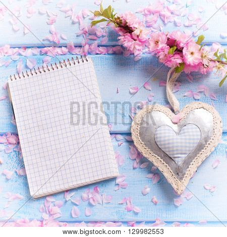Sakura pink flowers decorative heart and empty notebook on blue wooden planks. Selective focus. Place for text. Flat lay. Top view. Square image.