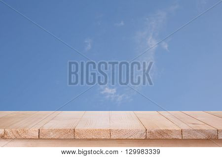 brown wood table top on blue sky with cloud background - can be used for montage or display your products