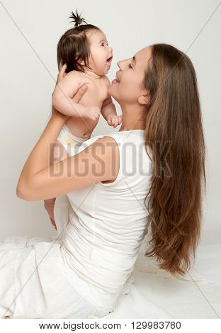 Mom throws baby baby and kiss, play and having fun