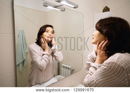 Senior Woman Applying Lotion Or Anti-aging Cream On Her Face Standing In Front Of The Mirror In The