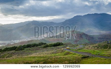 Taxi car traveling along the beautiful serpentine road through the fields and hills of Madeira island. Portugal.