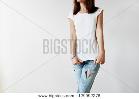 Cropped Isolated Shot Of Young Female Model In Trendy Ripped Denim Pants Stretching Her White Blank