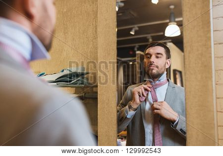 sale, shopping, fashion, style and people concept - happy young man choosing and tying tie on and looking to mirror in mall or clothing store