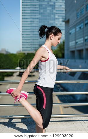 Young sport woman is stretching leg before jogging - outdoor in city
