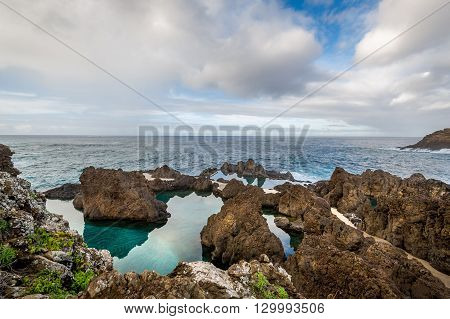 Natural volcanic rock pools on the shore of Atlantic ocean. Porto Moniz, popular touristic resort, Madeira island, Portugal.
