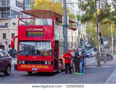 Melbourne, Australia - April 30, 2015: Two tourists asking a bus driver for information outside a sightseeing open top double decker bus stop in the city of Melbourne.