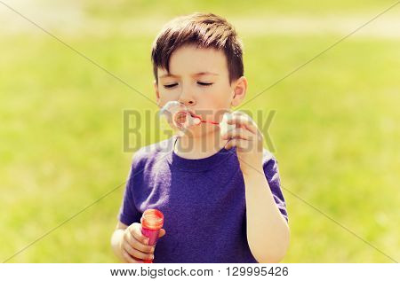 summer, childhood, leisure and people concept - little boy blowing soap bubbles outdoors