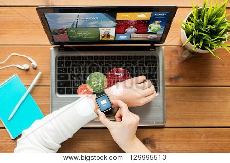 education, business, people, mass media and technology concept - close up of woman with smart watch and laptop computer on wooden table with internet application and e-mail message on screens