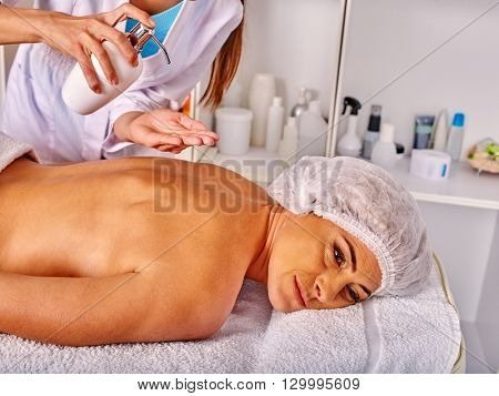 Woman middle-aged take back massage in spa salon with young beautician. Revitalizing massage.