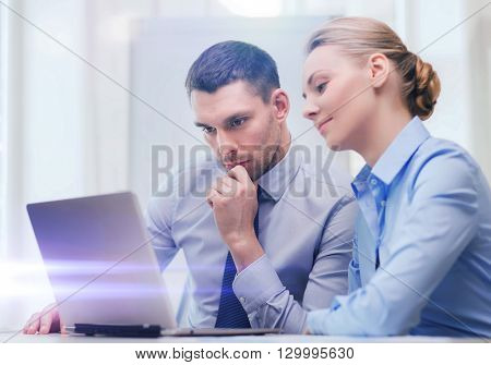 business, technology and office concept - serious businessman and businesswoman with laptop computer at office