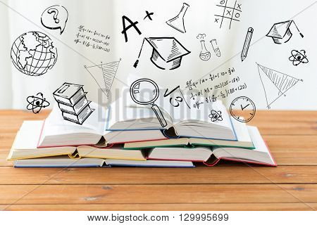 education, school, literature, reading and knowledge concept - close up of books on wooden table over school doodles