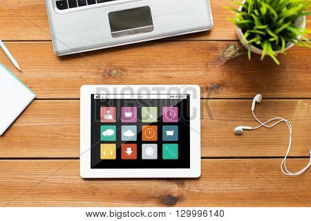 education, business, media and technology concept - close up of tablet pc computer, laptop and earphones on wooden table with menu icons on screen