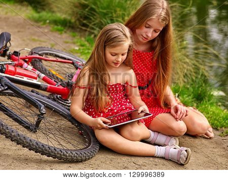 Bikes cycling girl. Two girls sisters  wearing red polka dots dress recreation near bicycle into park.  Children watch tablet pc. Girl in ecotourism.