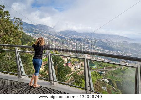 Woman looking at Madeira landscape from Cabo Girao famous viewpoint. Cabo Girao is the highest cliff in Europe. Madeira island, Portugal.