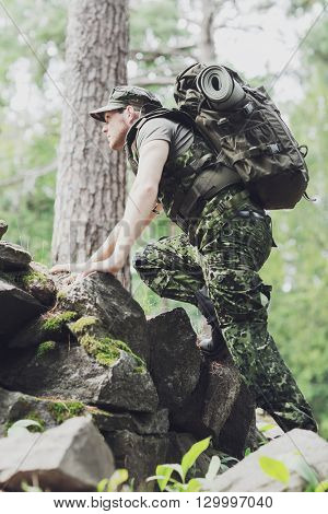 war, hiking, army and people concept - young soldier or ranger with backpack walking in forest