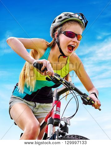 Bikes cycling girl. Girl rides bicycle aganist blue sky . Girl in cycling. Cycling is good for health. Cyclist looking down on green grass.